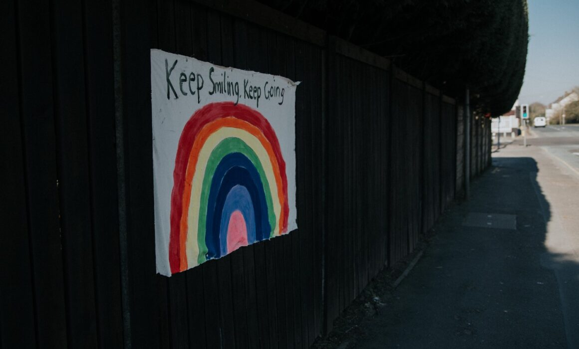 Poster stuck on a wall with a rainbow painted onto it. The words above the rainbow say 'keep smiling, keep going'.