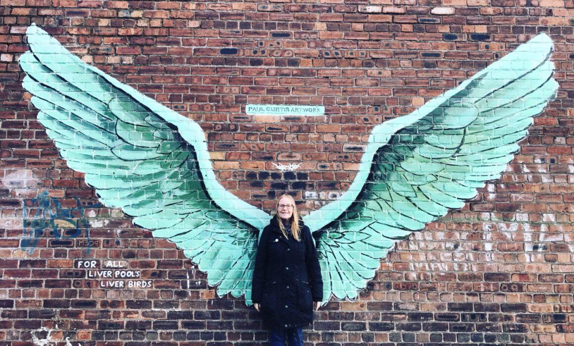 Marge stood in front of angel wings street art.