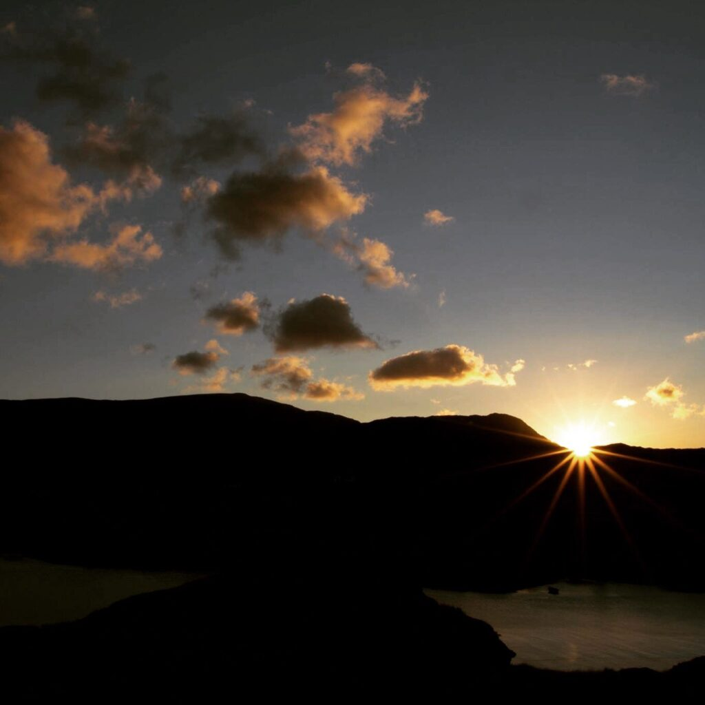 Photograph of clouds and hills at sunset.