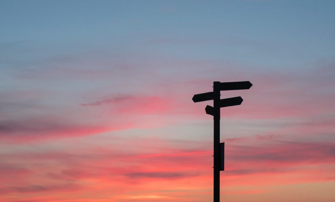 Silhouette of signposts in front of a red/blue sunset.